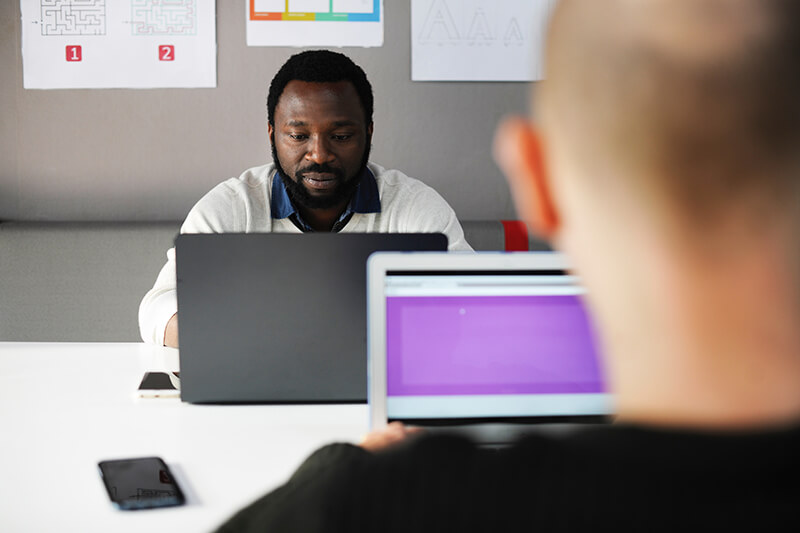 African man working on laptop while engaging in critical thinking skills